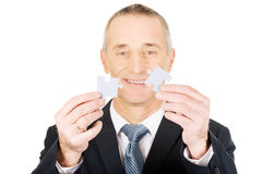 Businessman trying to connect puzzle pieces. Royalty Free Stock Photography