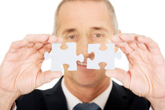 Businessman trying to connect puzzle pieces. Stock Image