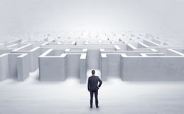 Businessman choosing between entrances at the edge of a maze stock illustration