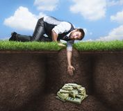 Businessman trying to get treasure in the soil Royalty Free Stock Photography