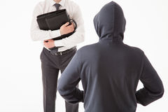 Businessman trying to hide his briefcase by unknown man Stock Image