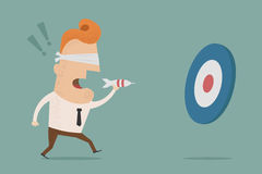 Businessman trying to hit a target with darts Royalty Free Stock Photography