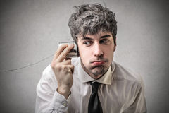 Businessman trying to listen to something. Young businessman trying to listen to something through a metal glass Stock Image