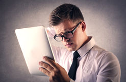 Businessman trying to read something on the tablet Stock Photography