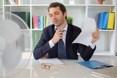 Businessman trying to refresh at work in summer heat. Office employee feeling stressed after summer heat haze Stock Photo