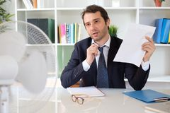Office employee feeling stressed after summer heat haze. Businessman trying to refresh at work in summer heat Stock Image