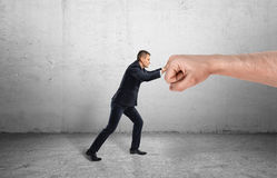 Businessman trying to resist huge male fist and move it away on grey background Royalty Free Stock Photos