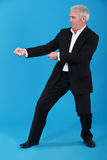 Businessman tugging invisible rope. Businessman tugging empty copy space royalty free stock image