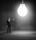 Businessman turn on bulb Stock Photos