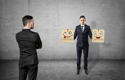 Businessman with a turned back on concrete background looking at another man holding two boxes with drawn faces. Stock Image