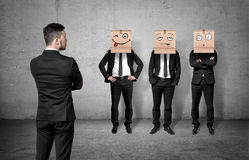 Businessman turned back and looking at three men wearing carton boxes on their heads. Royalty Free Stock Photography