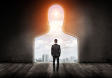 A businessman with turned back looks out of a hole in a wall made in shape of a human head. Stock Images