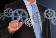 Businessman turning cogwheels Stock Photography