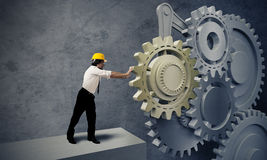 Businessman turning a gear system Stock Images