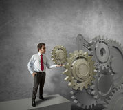Businessman turning a gear system Stock Photography