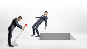 A businessman turns a large lever switch while another man falls back to an open square hole in the ground. Royalty Free Stock Photography