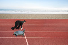 Businessman and turtle are ready to race on running track. With natural sea beach background. Turtle race competing metaphor concept Stock Photo
