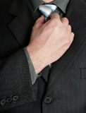 Businessman tweaking his tie. With a hand Royalty Free Stock Photography