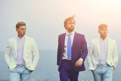 Businessman and twins guys walking on blue sky, agile business. Businessman or man and twins guys in business formal outfit walking on blue sky background royalty free stock photography