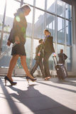 Businessman and two businesswoman with trolley. At the airport Royalty Free Stock Photo