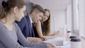 Businessman and two businesswomen working on paper graphs in the office, slow motion. Concept: people, business, finance, management, marketing, colleagues stock video
