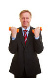 Businessman with two dumbbells. Senior businessman exercising with two orange dumbbells Royalty Free Stock Photography