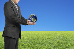Businessman two hands hold ball with global map with fresh green. Meadow and clear blue sky royalty free stock image
