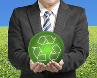 Businessman two hands hold green ball with recycle symbol with g. Reen meadow and blue sky background Stock Photos