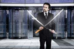 Businessman with two Japanese swords at the entrance of an offic Stock Images