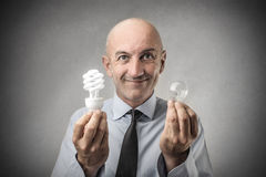 Businessman with two light bulbs royalty free stock photography