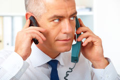 Businessman with two phones Stock Photos