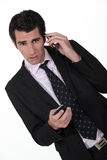 Businessman with two phones. Stock Photo