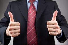 Man with two thumbs up. Businessman with two thumbs up. Neutral background Royalty Free Stock Image