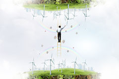 Businessman between two worlds. Businessman standing on ladder between two ecological energy realities Stock Photography