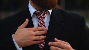 Businessman tying the necktie outdoors stock video