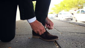 Businessman tying up his shoelaces stock video footage