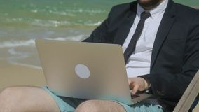 Businessman is typing a business email on his computer while being on the beach. Man in black jacket, tie and shorts is sitting in deck-chair near the sea and stock footage