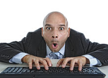 Businessman typing on computer keyboard with funny face expressi Royalty Free Stock Image