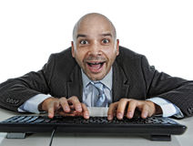 Businessman typing on computer keyboard with funny face expressi Stock Images