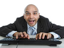 Businessman typing on computer keyboard with funny face expressi Stock Photos