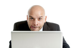 Businessman typing on computer keyboard with funny face expression Royalty Free Stock Images
