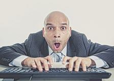 Businessman typing on computer keyboard with funny face expression Royalty Free Stock Image