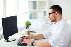Businessman typing on computer keyboard at office Stock Images