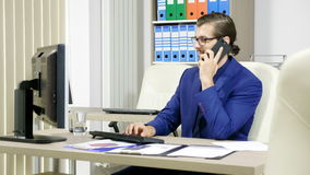 Businessman typing on the computer and talking on the phone. Business and corporate stock footage