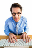Businessman typing on his keyboard wearing glasses. On white background Royalty Free Stock Photos