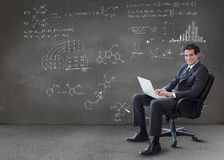 Businessman typing on his laptop with maths equations on wall. In grey empty room Royalty Free Stock Photo