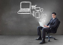 Businessman typing on his laptop with media device graphics comi Royalty Free Stock Images