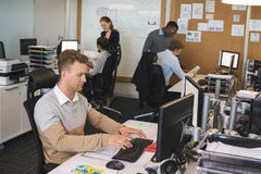 Businessman typing on keyboard while colleagues working in background Royalty Free Stock Photos