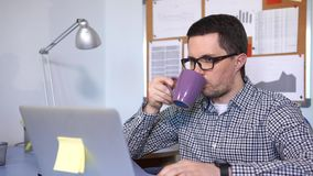 Businessman typing on keyboard, looking at the screen and drinking coffee. Classical office scene stock video footage