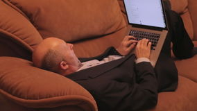 Businessman typing on a keyboard. Man typing while lying on sofa. Dolly, locked down, close-up, low-key, artificial light, indoors. Male is texting on laptop stock footage